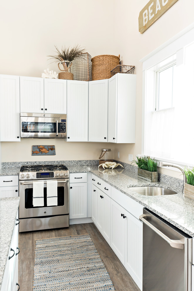 Example of a large beach style l-shaped dark wood floor eat-in kitchen design in Boston with an undermount sink, recessed-panel cabinets, white cabinets, granite countertops, stainless steel appliances and an island