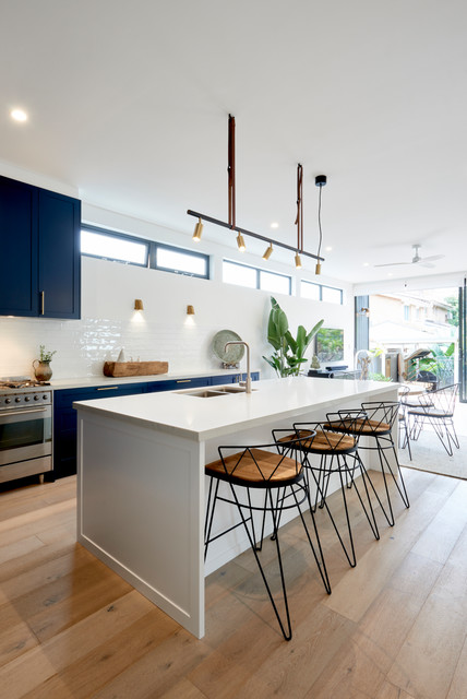 Photo of a contemporary galley eat-in kitchen in Sydney with an undermount sink, shaker cabinets, black cabinets, white splashback, stainless steel appliances, medium hardwood floors, an island, brown floor and white benchtop.