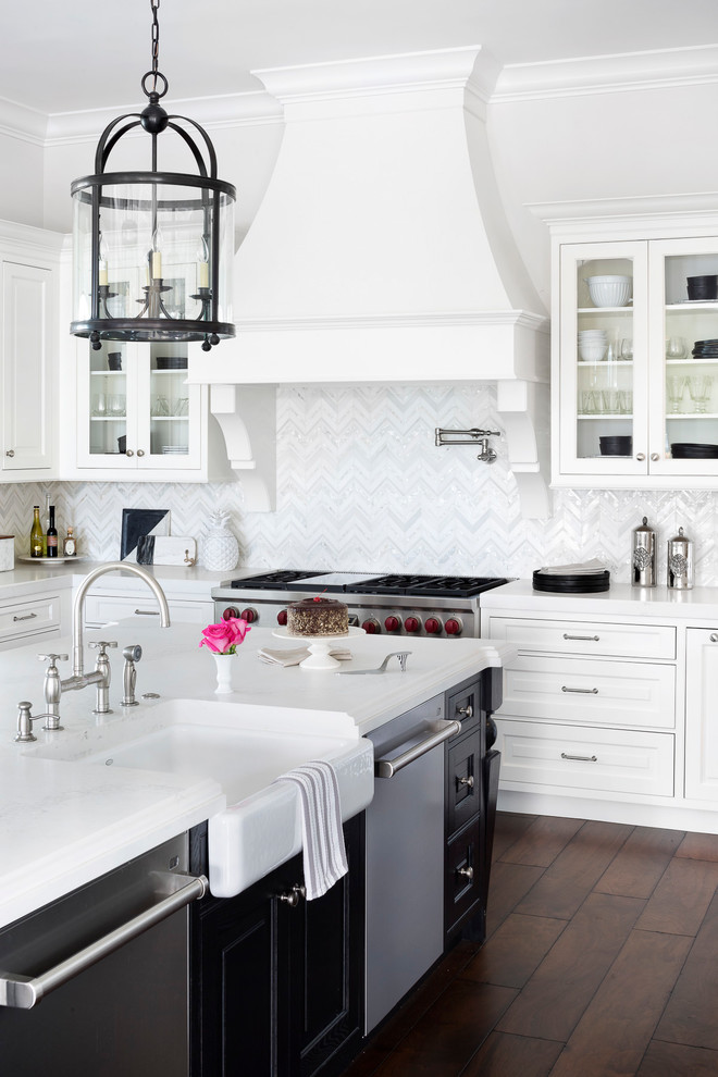 Example of a transitional dark wood floor and brown floor kitchen design in Miami with a farmhouse sink, raised-panel cabinets, white cabinets, white backsplash, stainless steel appliances, an island and white countertops