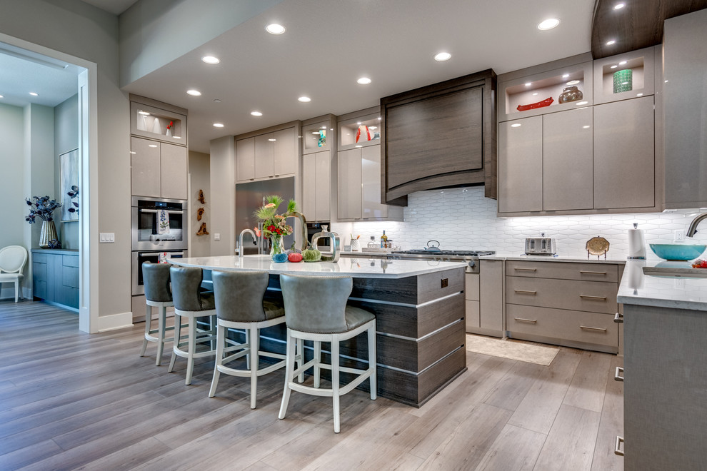 Example of a trendy u-shaped gray floor kitchen design in Portland with an undermount sink, flat-panel cabinets, gray cabinets, white backsplash, stainless steel appliances, an island and white countertops