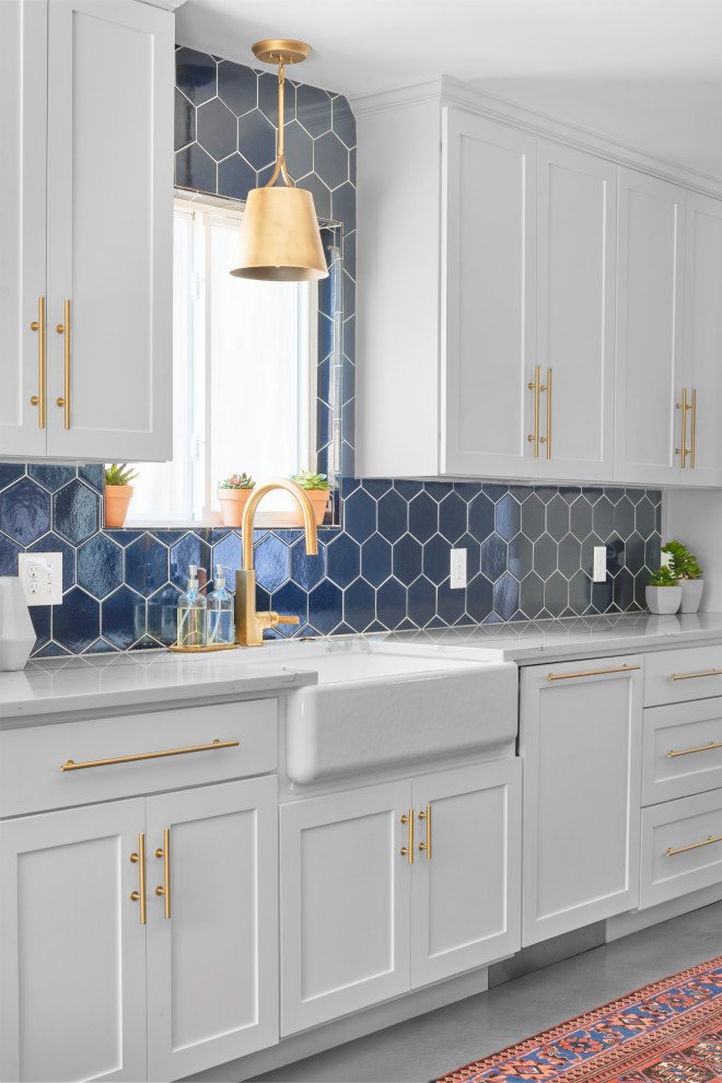 Kitchen - large transitional single-wall gray floor kitchen idea in Austin with white cabinets, blue backsplash, ceramic backsplash, an island and white countertops