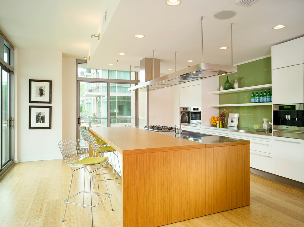 Minimalist kitchen photo in Atlanta with flat-panel cabinets, green backsplash, glass sheet backsplash and white cabinets