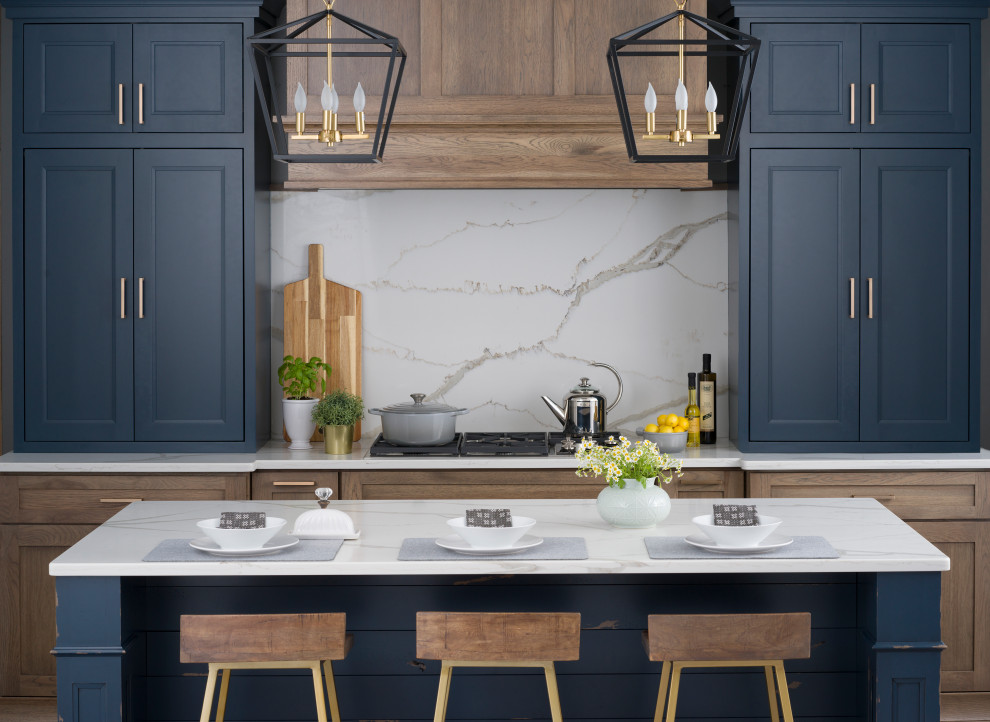 Open concept kitchen - mid-sized country medium tone wood floor and brown floor open concept kitchen idea in Boston with a farmhouse sink, flat-panel cabinets, blue cabinets, quartz countertops, white backsplash, stone slab backsplash, stainless steel appliances, an island and brown countertops