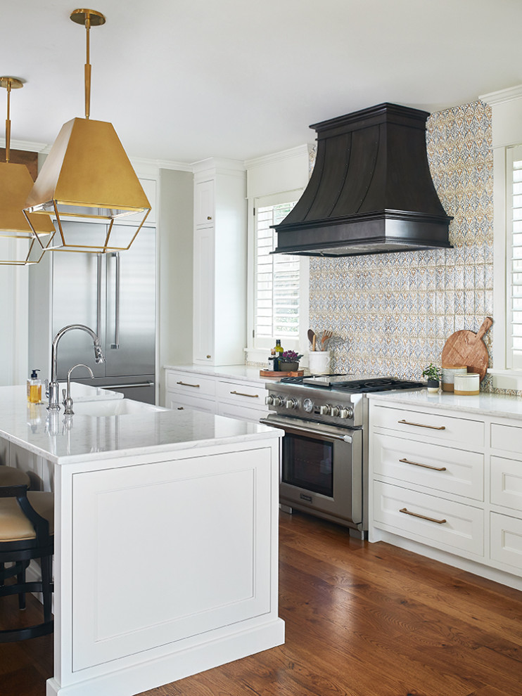 Eat-in kitchen - small coastal l-shaped medium tone wood floor and brown floor eat-in kitchen idea in Grand Rapids with white cabinets, quartz countertops, ceramic backsplash, stainless steel appliances, white countertops, a farmhouse sink, flat-panel cabinets, multicolored backsplash and an island