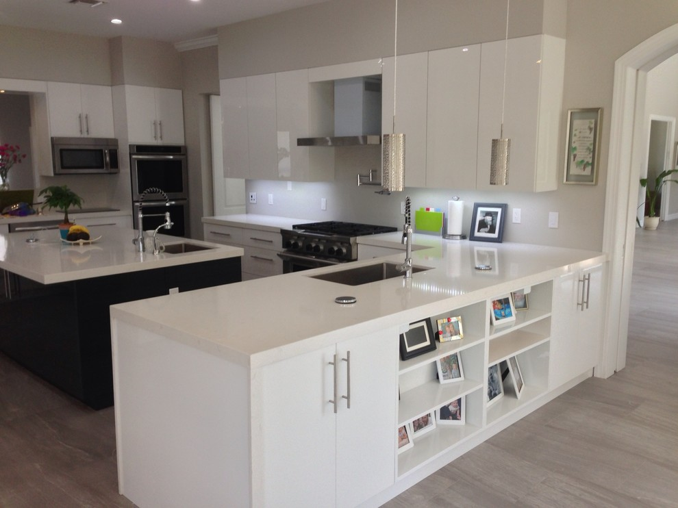 Example of a huge minimalist u-shaped porcelain tile open concept kitchen design in Miami with an undermount sink, flat-panel cabinets, white cabinets, quartz countertops, white backsplash, stainless steel appliances and an island