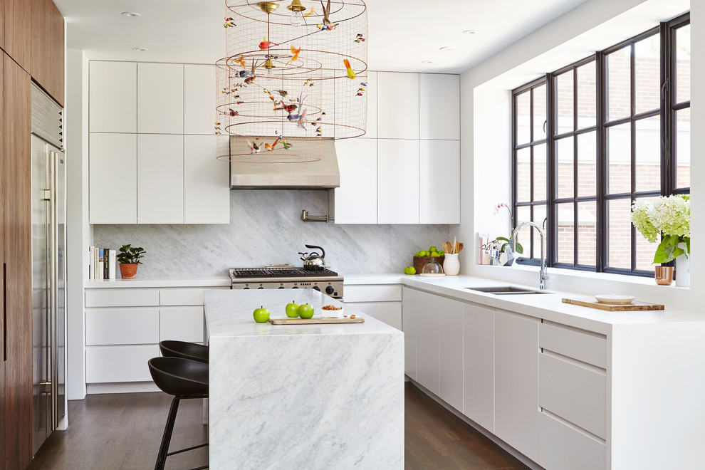 Mid-sized trendy u-shaped medium tone wood floor and brown floor open concept kitchen photo in Toronto with flat-panel cabinets, white cabinets, quartz countertops, gray backsplash, stone slab backsplash, stainless steel appliances, an island and a double-bowl sink