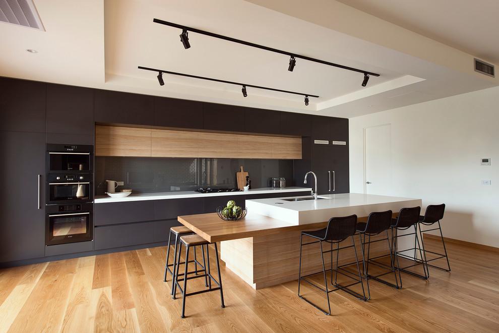 Ispirazione per una cucina a corridoio moderna di medie dimensioni con lavello sottopiano, ante lisce, paraspruzzi grigio, paraspruzzi con lastra di vetro, elettrodomestici neri, pavimento in legno massello medio, isola, ante nere e top bianco