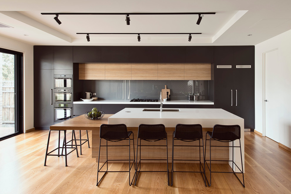 Idée de décoration pour une grande cuisine américaine parallèle minimaliste avec un évier encastré, un placard à porte plane, des portes de placard noires, une crédence en feuille de verre, un électroménager noir, un îlot central et un sol en bois brun.