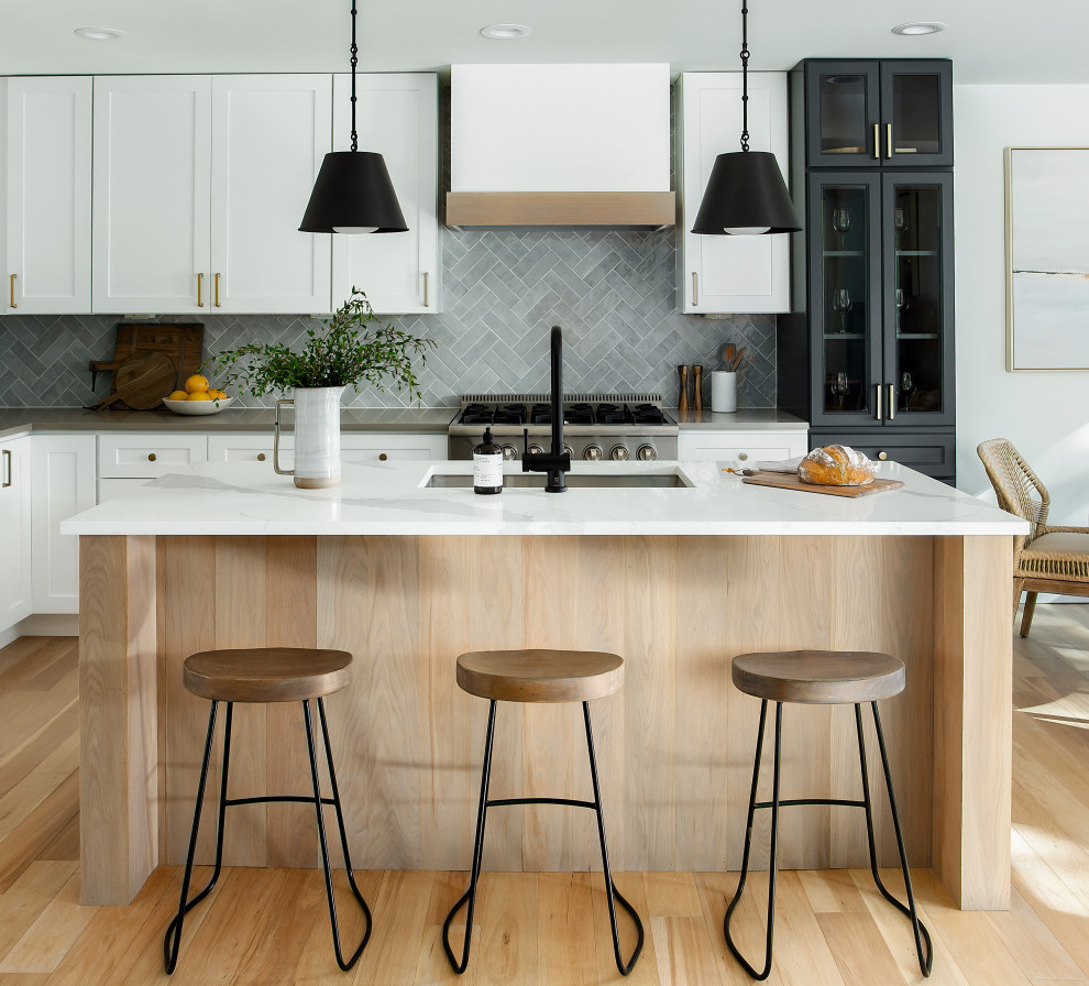 Example of a mid-sized beach style l-shaped light wood floor and beige floor eat-in kitchen design in Dallas with a single-bowl sink, shaker cabinets, quartz countertops, gray backsplash, porcelain backsplash, stainless steel appliances, an island, white countertops and white cabinets