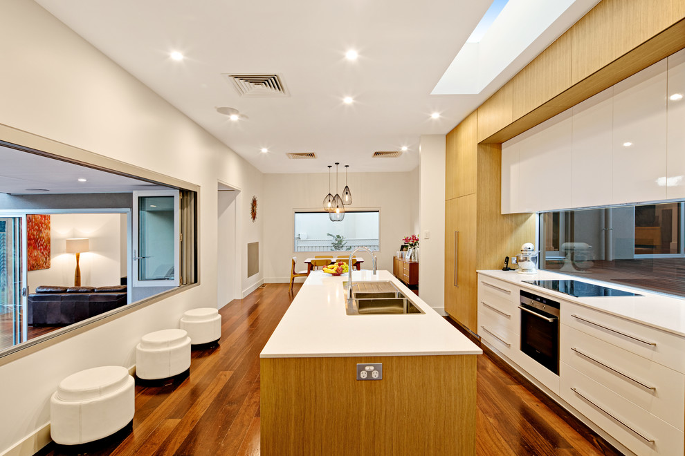 Design ideas for a contemporary kitchen in Adelaide with a drop-in sink, flat-panel cabinets, white cabinets, glass tile splashback, stainless steel appliances, dark hardwood floors and an island.