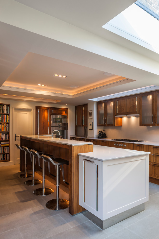 Inspiration for a mid-sized contemporary kitchen remodel in London with an island, glass-front cabinets, quartz countertops, stainless steel appliances and medium tone wood cabinets