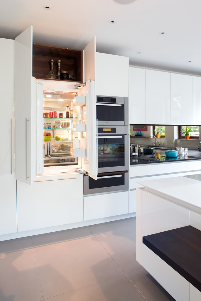 Inspiration for a contemporary kitchen remodel in London with flat-panel cabinets, white cabinets, mirror backsplash, paneled appliances and an island