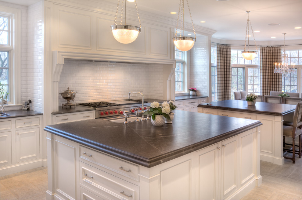 Large transitional u-shaped slate floor eat-in kitchen photo in Chicago with a farmhouse sink, recessed-panel cabinets, white cabinets, white backsplash, stainless steel appliances, two islands, soapstone countertops and subway tile backsplash