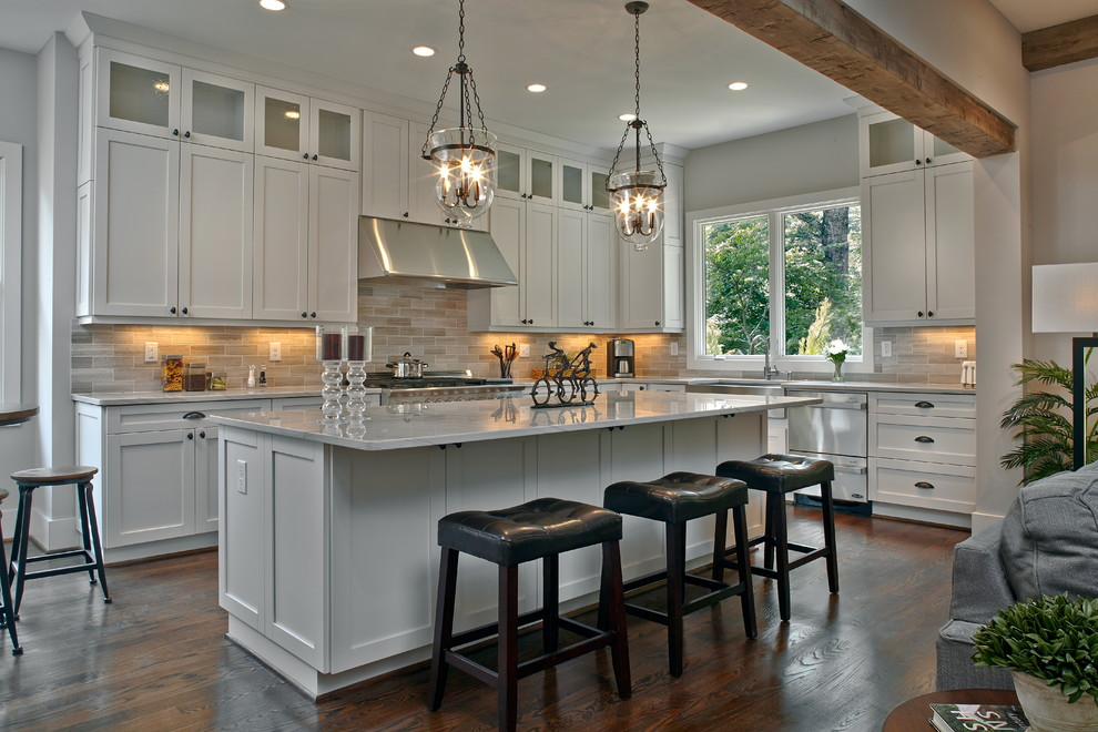 Example of a large classic l-shaped dark wood floor open concept kitchen design in Atlanta with a farmhouse sink, shaker cabinets, white cabinets, marble countertops, gray backsplash, stainless steel appliances, an island and white countertops