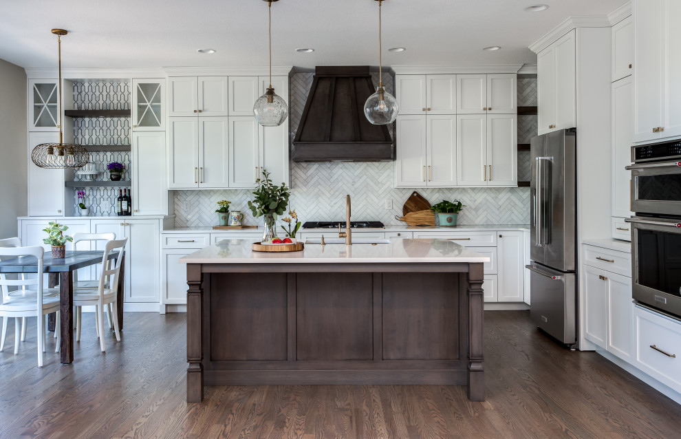 Example of a large transitional l-shaped medium tone wood floor and brown floor open concept kitchen design in Denver with an undermount sink, shaker cabinets, white cabinets, quartz countertops, beige backsplash, marble backsplash, stainless steel appliances, an island and white countertops