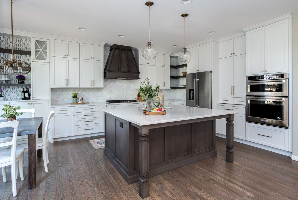 Large transitional galley medium tone wood floor and brown floor open concept kitchen photo in Denver with an undermount sink, shaker cabinets, white cabinets, quartz countertops, beige backsplash, marble backsplash, stainless steel appliances, an island and white countertops