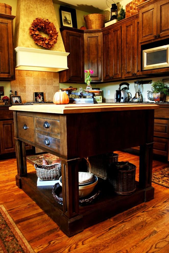 Elegant kitchen photo in Austin with wood countertops, raised-panel cabinets, dark wood cabinets and beige backsplash