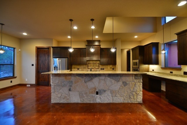 Example of a mid-sized trendy l-shaped concrete floor eat-in kitchen design in Austin with an island, recessed-panel cabinets, dark wood cabinets, granite countertops, beige backsplash, ceramic backsplash and stainless steel appliances