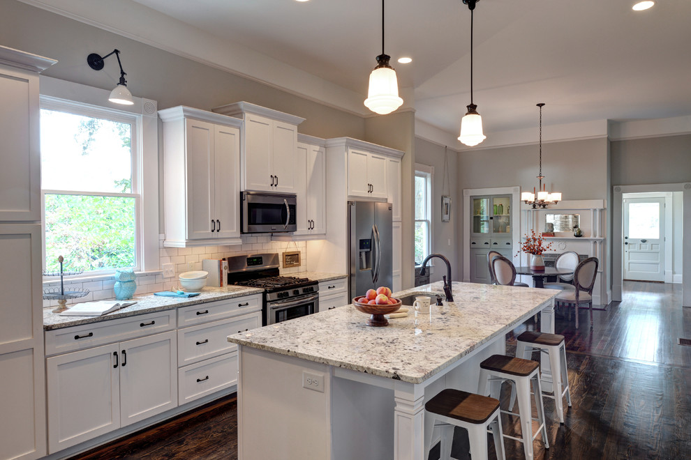 Example of a mid-sized classic galley dark wood floor eat-in kitchen design in Atlanta with an undermount sink, shaker cabinets, dark wood cabinets, granite countertops, white backsplash, ceramic backsplash, stainless steel appliances and an island
