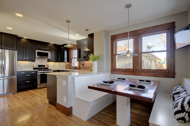 Example of a mid-sized eclectic light wood floor and brown floor eat-in kitchen design in Denver with stainless steel appliances, shaker cabinets, dark wood cabinets, red backsplash, brick backsplash and a peninsula