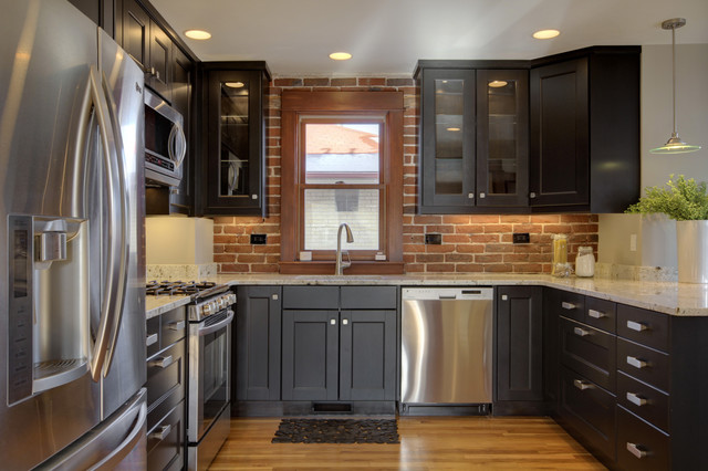 Inspiration for a mid-sized eclectic light wood floor and brown floor eat-in kitchen remodel in Denver with shaker cabinets, red backsplash, brick backsplash, stainless steel appliances, a peninsula and black cabinets