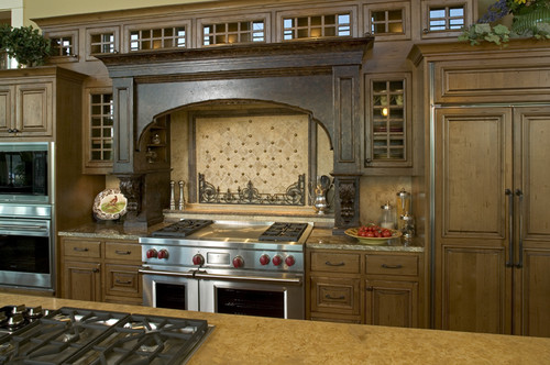 This dream kitchen features multiple stove tops.