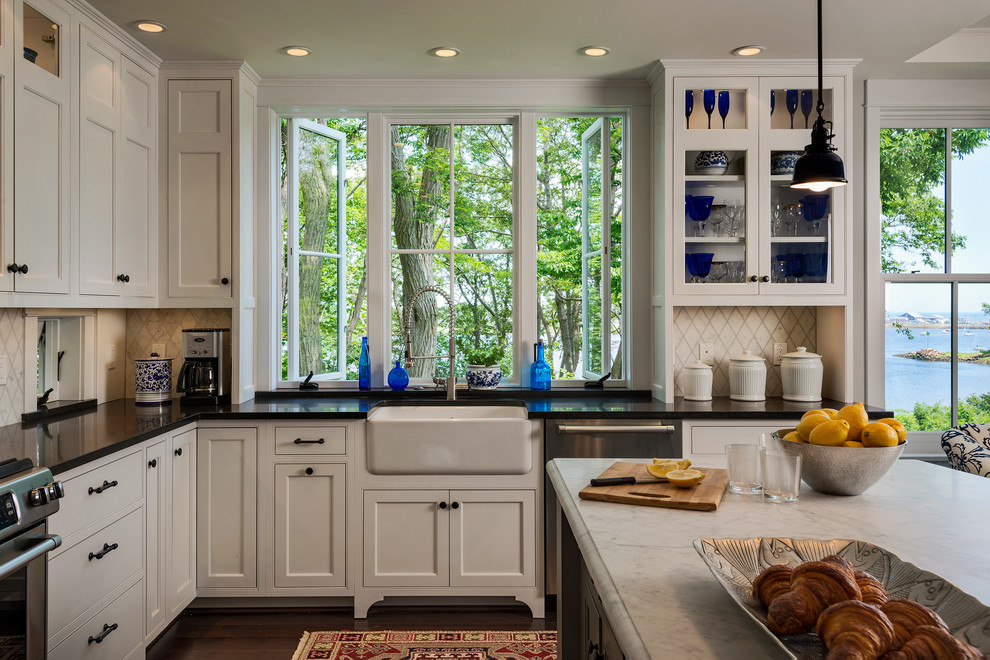 Coastal l-shaped eat-in kitchen photo in Portland Maine with a farmhouse sink, beaded inset cabinets, white cabinets, granite countertops, white backsplash, stone tile backsplash and stainless steel appliances