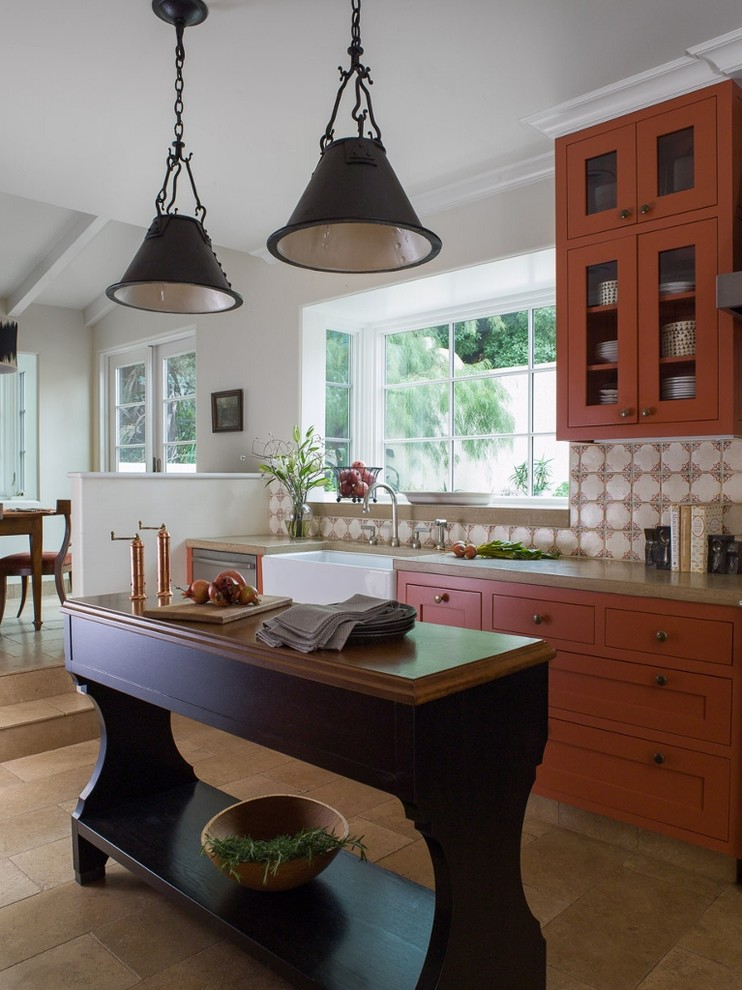 Inspiration for a mid-sized mediterranean galley limestone floor and brown floor eat-in kitchen remodel in San Francisco with a farmhouse sink, orange cabinets, recessed-panel cabinets, concrete countertops, multicolored backsplash, terra-cotta backsplash, stainless steel appliances and an island