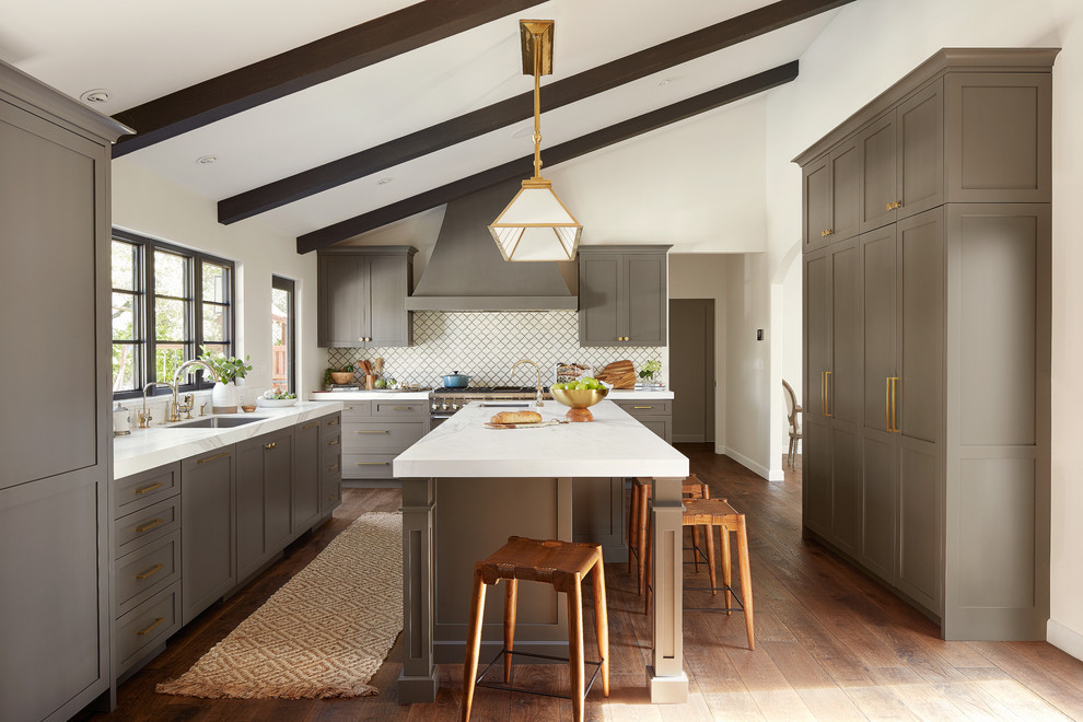 Example of a tuscan u-shaped dark wood floor and brown floor kitchen design in San Francisco with an undermount sink, shaker cabinets, gray cabinets, white backsplash, an island and white countertops