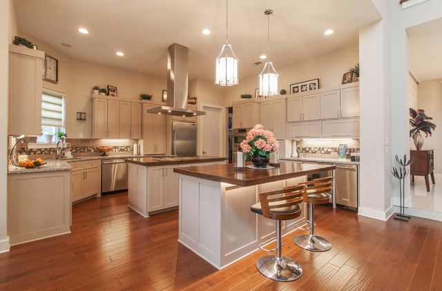 Kitchen - contemporary medium tone wood floor kitchen idea in Dallas with an undermount sink, shaker cabinets, gray cabinets, wood countertops, beige backsplash, ceramic backsplash, stainless steel appliances and two islands