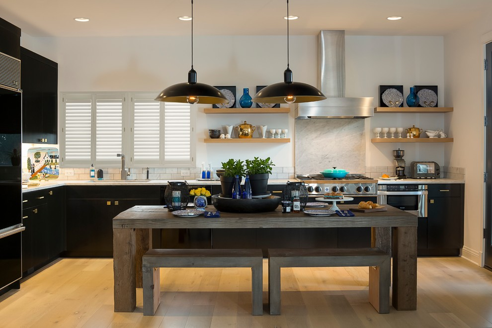 Inspiration for a mid-sized transitional l-shaped light wood floor eat-in kitchen remodel in Los Angeles with flat-panel cabinets, black cabinets, white backsplash and stone slab backsplash