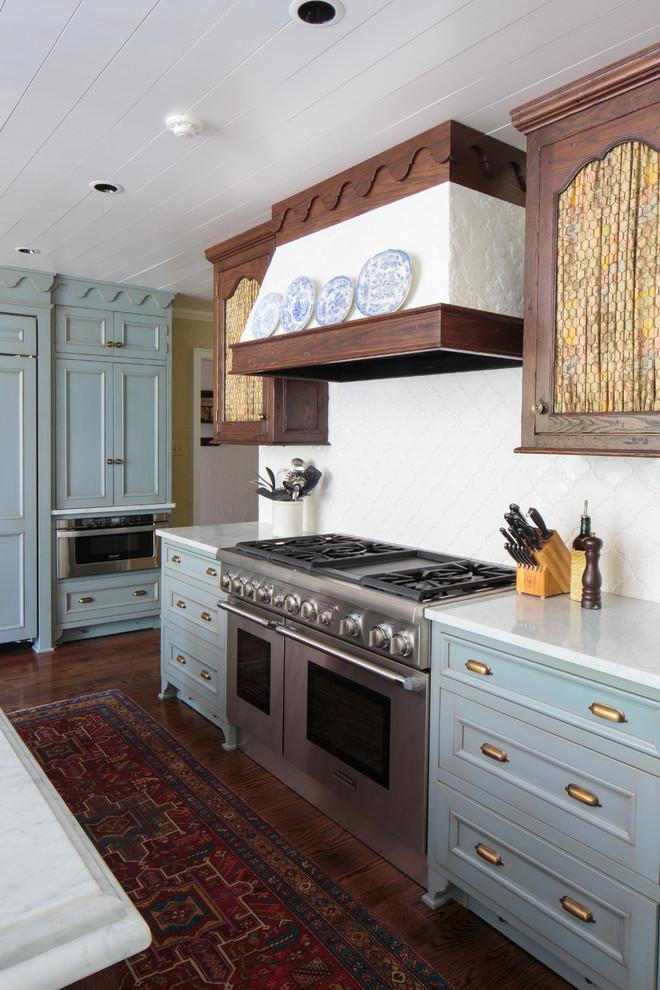 Modelo de cocina clásica con armarios con paneles empotrados, puertas de armario azules, salpicadero blanco, electrodomésticos de acero inoxidable, suelo de madera oscura y una isla