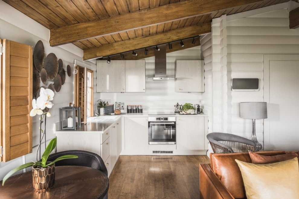 Example of a small farmhouse l-shaped medium tone wood floor and brown floor open concept kitchen design in Other with flat-panel cabinets, light wood cabinets, no island and white countertops