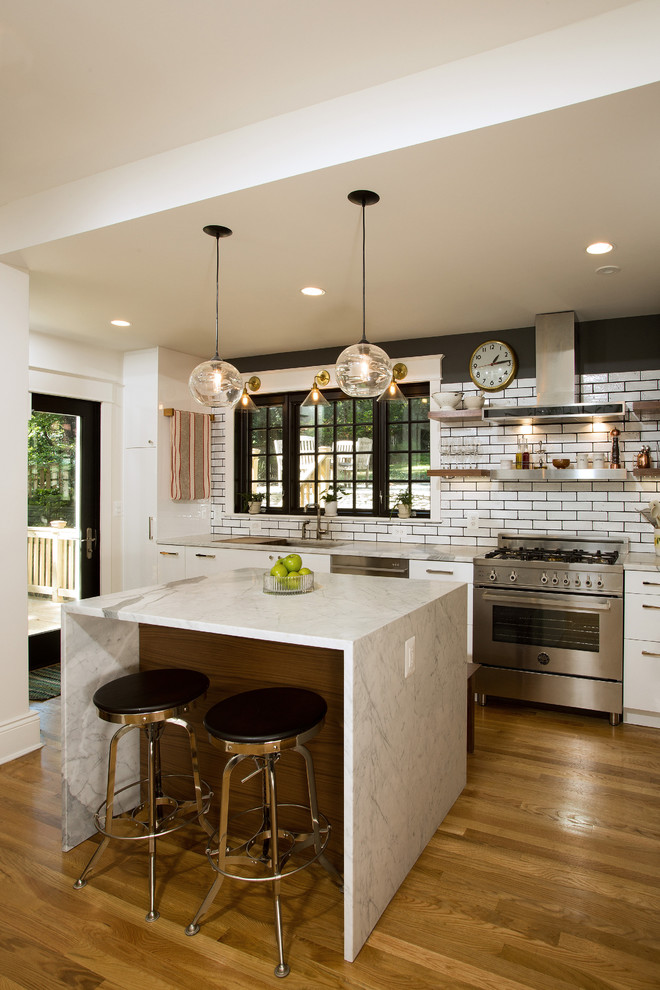 Inspiration for a mid-sized transitional medium tone wood floor kitchen remodel in DC Metro with an undermount sink, flat-panel cabinets, white cabinets, granite countertops, white backsplash, stainless steel appliances, an island and subway tile backsplash