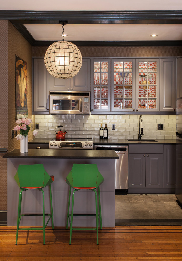 Inspiration for a transitional kitchen remodel in Philadelphia with an undermount sink, glass-front cabinets, gray cabinets, white backsplash, subway tile backsplash, stainless steel appliances and a peninsula