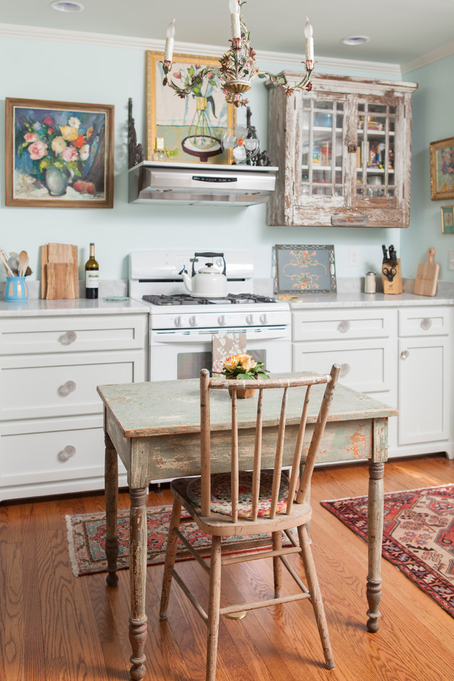 Inspiration for a shabby-chic style eat-in kitchen remodel in Wilmington with recessed-panel cabinets, distressed cabinets, white appliances and marble countertops
