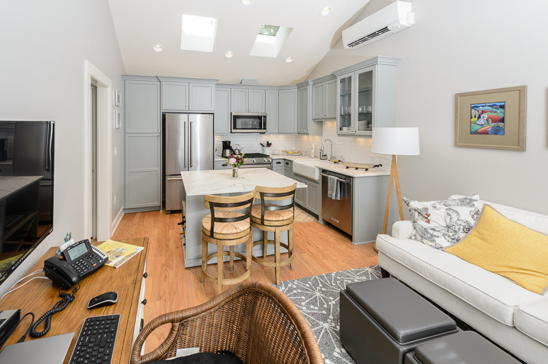 Open concept kitchen - small craftsman l-shaped medium tone wood floor open concept kitchen idea in Portland with a farmhouse sink, shaker cabinets, gray cabinets, quartz countertops, white backsplash, matchstick tile backsplash, stainless steel appliances and an island