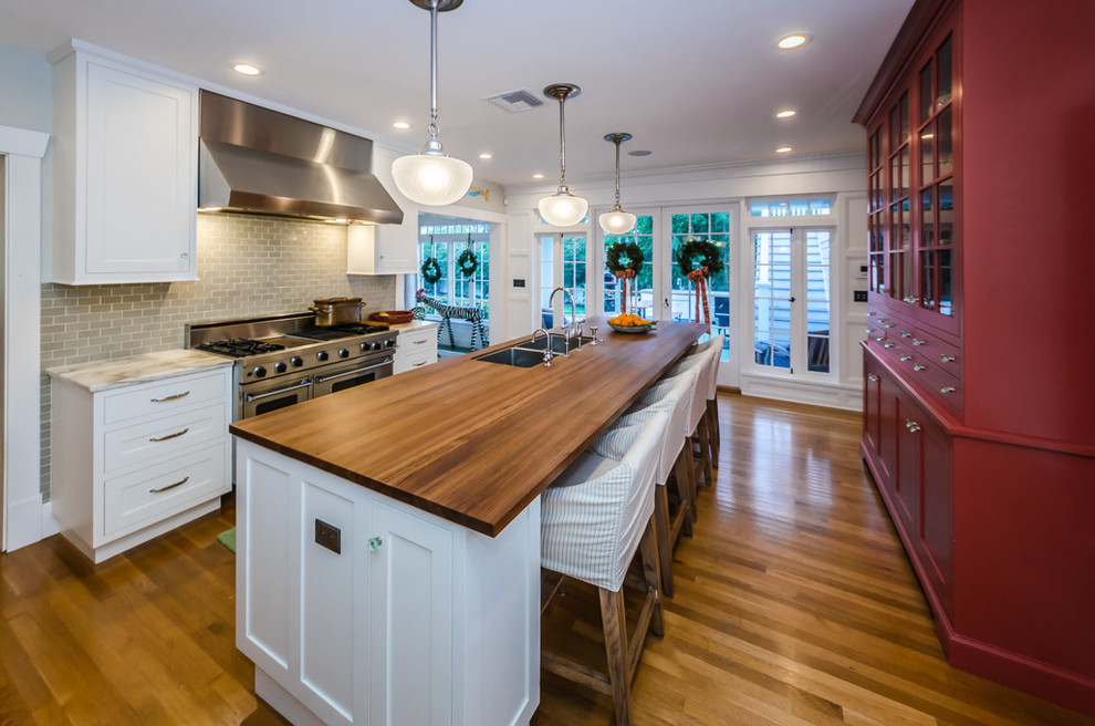 Example of a classic galley medium tone wood floor and brown floor kitchen design in Tampa with an undermount sink, shaker cabinets, white cabinets, wood countertops, gray backsplash, subway tile backsplash, stainless steel appliances, an island and brown countertops