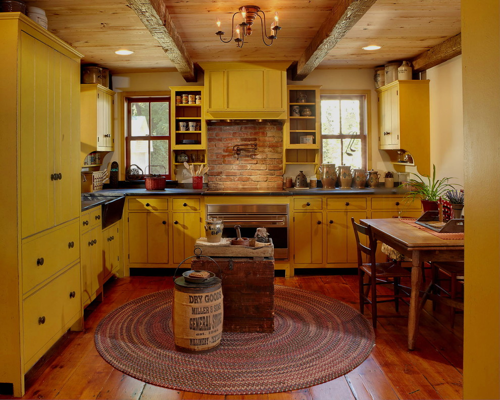 Cottage l-shaped medium tone wood floor enclosed kitchen photo in New York with yellow cabinets, no island, a farmhouse sink and colored appliances