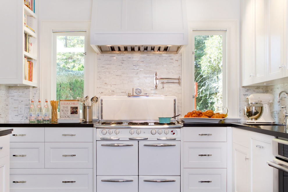 Example of a transitional kitchen design in Los Angeles with recessed-panel cabinets, white appliances, stone tile backsplash and white cabinets