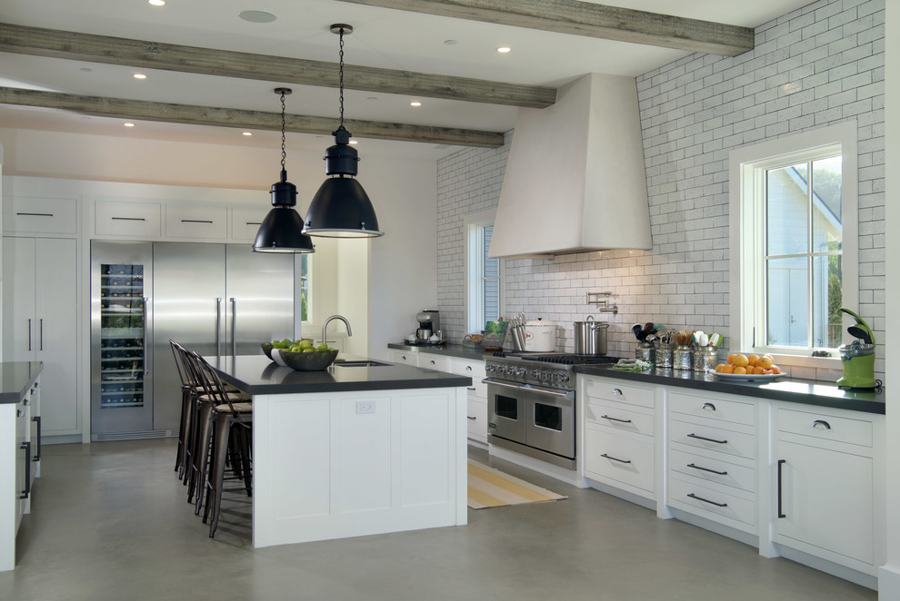 Inspiration for a farmhouse concrete floor kitchen remodel in San Francisco with an undermount sink, flat-panel cabinets, white cabinets, white backsplash, subway tile backsplash, stainless steel appliances and an island