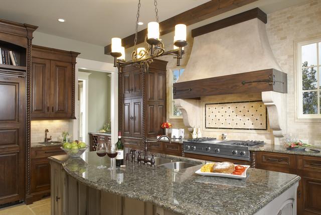 Spanish style kitchen with off white base cabinets dark island terra cotta  floors