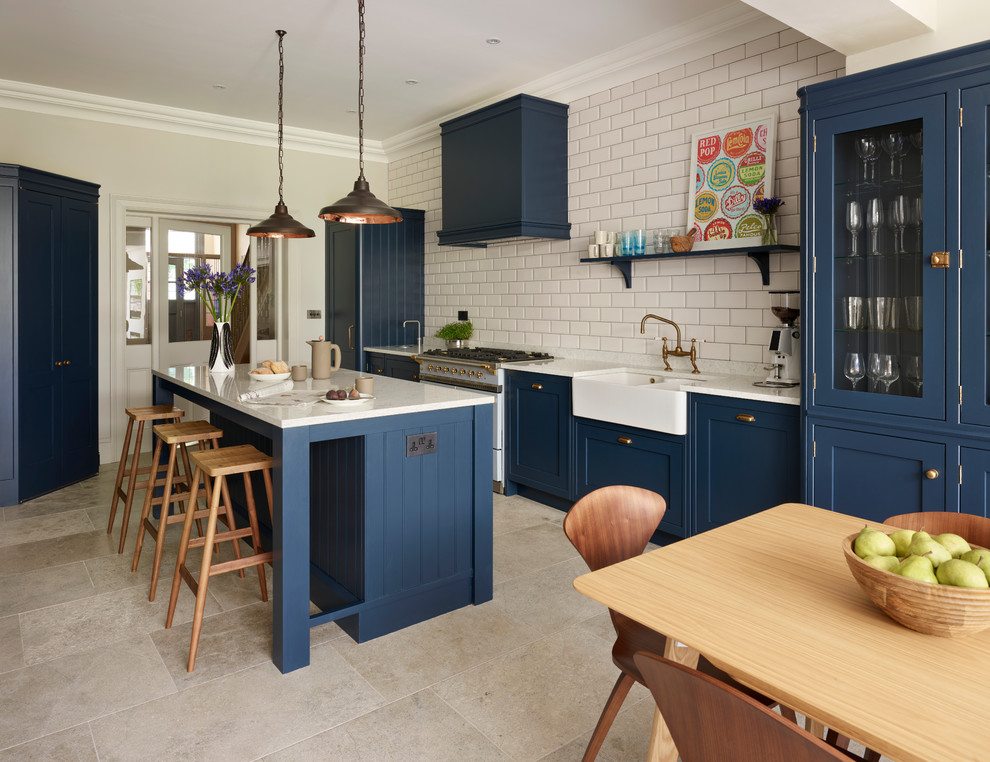 Transitional eat-in kitchen photo in Sussex with a farmhouse sink, white backsplash, subway tile backsplash, an island, glass-front cabinets and blue cabinets