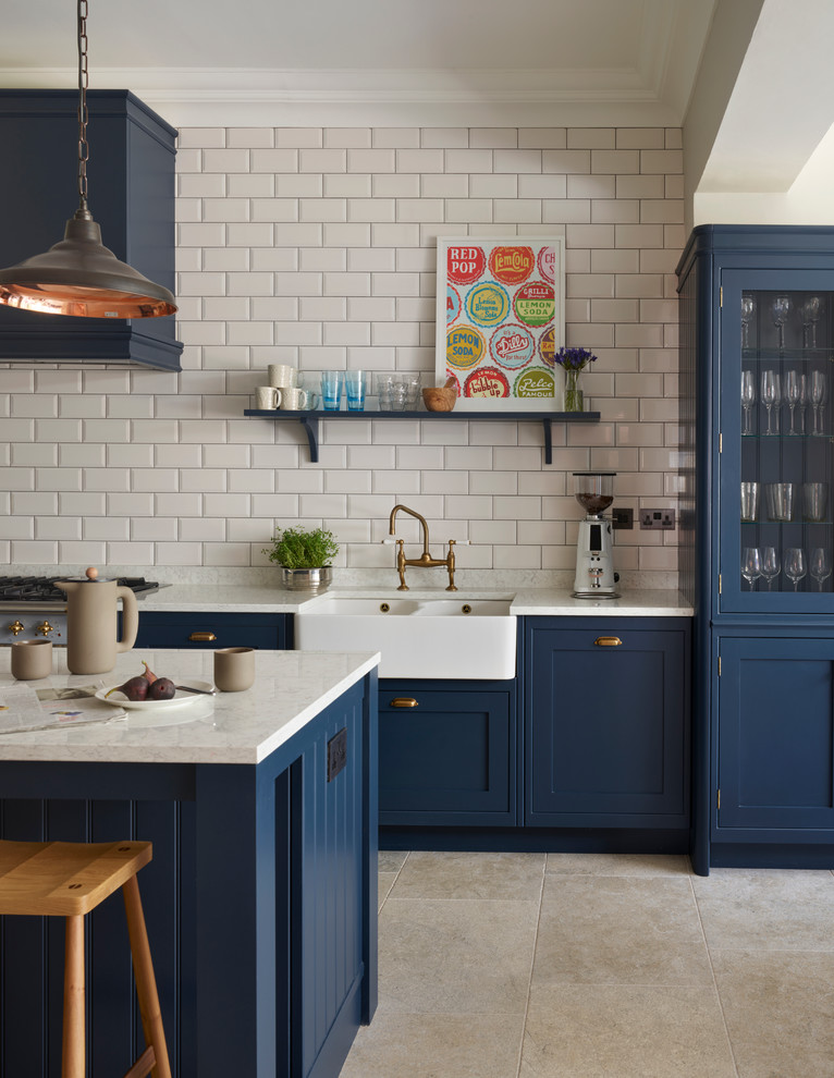 Kitchen - mid-sized transitional kitchen idea in Sussex with a farmhouse sink, white backsplash, subway tile backsplash, stainless steel appliances and an island
