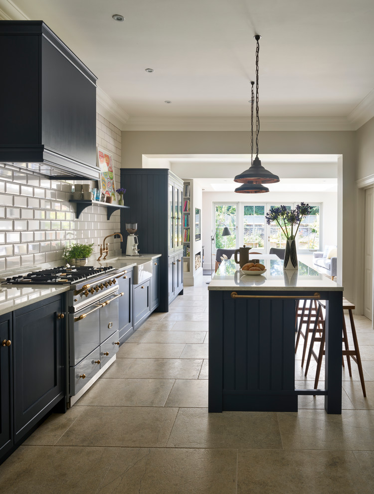 Example of a mid-sized transitional kitchen design in Sussex with a farmhouse sink, white backsplash, subway tile backsplash, stainless steel appliances and an island