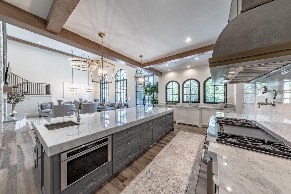 Example of a large tuscan porcelain tile and brown floor open concept kitchen design in Salt Lake City with an undermount sink, recessed-panel cabinets, white cabinets, marble countertops, gray backsplash, marble backsplash, paneled appliances and an island