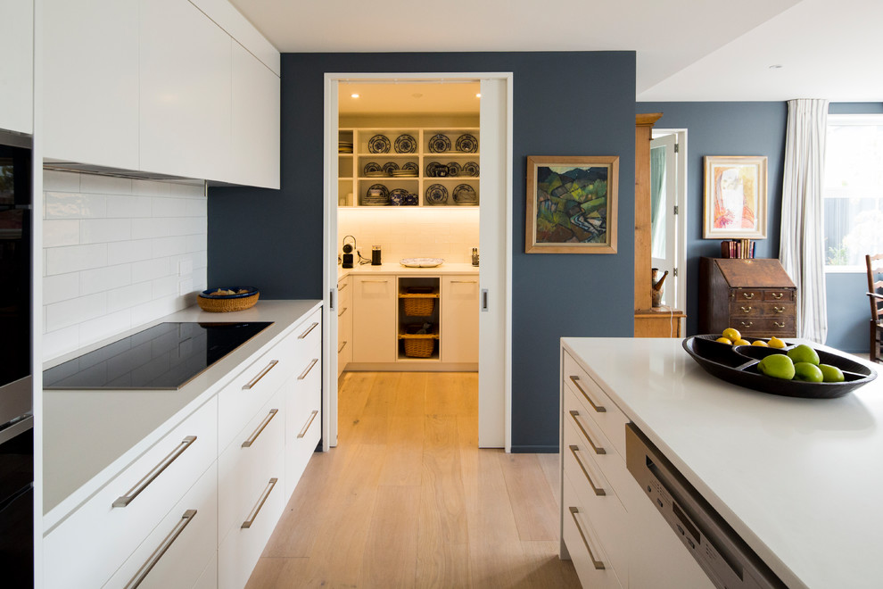 Inspiration for a mid-sized contemporary galley light wood floor and brown floor kitchen remodel in Christchurch with an undermount sink, white cabinets, quartz countertops, white backsplash, porcelain backsplash, paneled appliances, an island and flat-panel cabinets