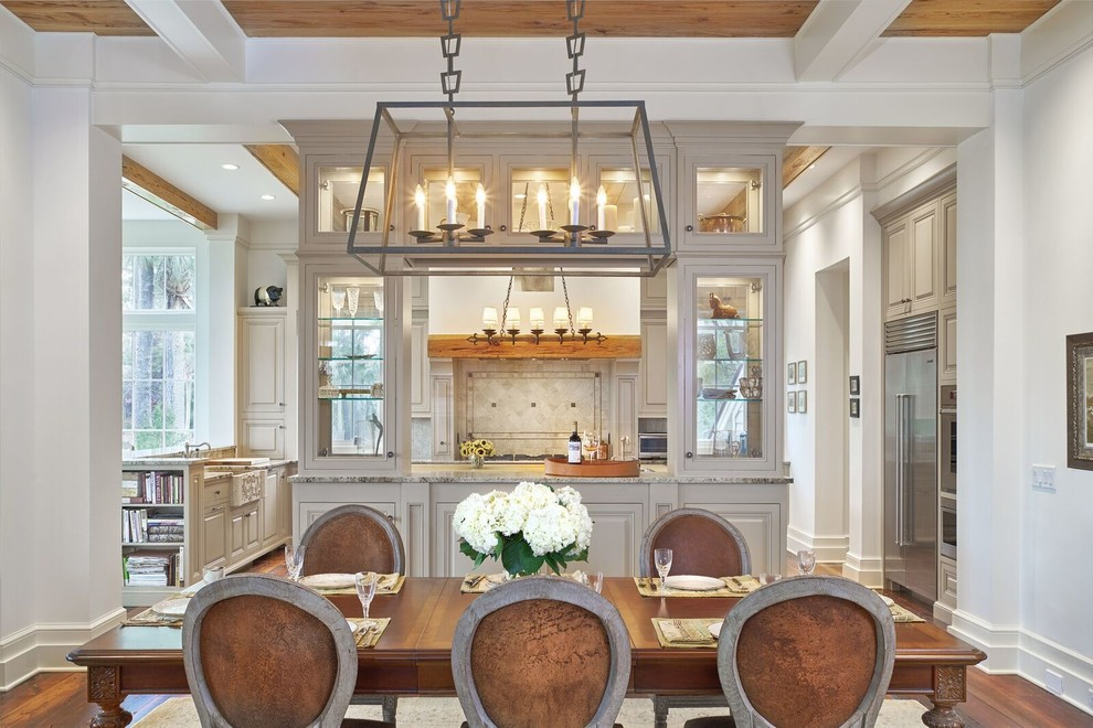 Eat-in kitchen - large traditional u-shaped medium tone wood floor eat-in kitchen idea in Atlanta with a farmhouse sink, raised-panel cabinets, gray cabinets, granite countertops, beige backsplash, stone tile backsplash, stainless steel appliances and two islands