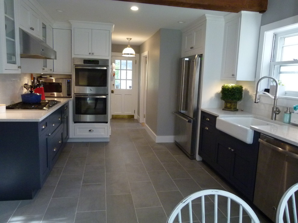 Inspiration for a mid-sized farmhouse galley concrete floor and gray floor eat-in kitchen remodel in New York with a farmhouse sink, shaker cabinets, white cabinets, solid surface countertops, white backsplash, terra-cotta backsplash, stainless steel appliances, no island and white countertops
