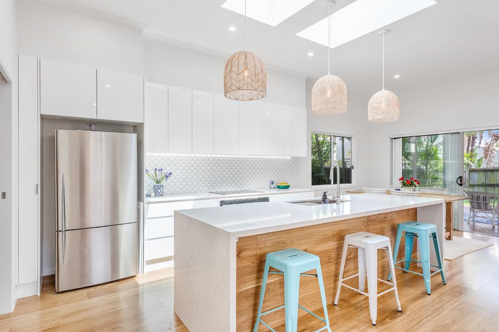 Идея дизайна: параллельная кухня с обеденным столом, врезной раковиной, плоскими фасадами, белыми фасадами, белым фартуком, техникой под мебельный фасад, светлым паркетным полом, островом и белой столешницей